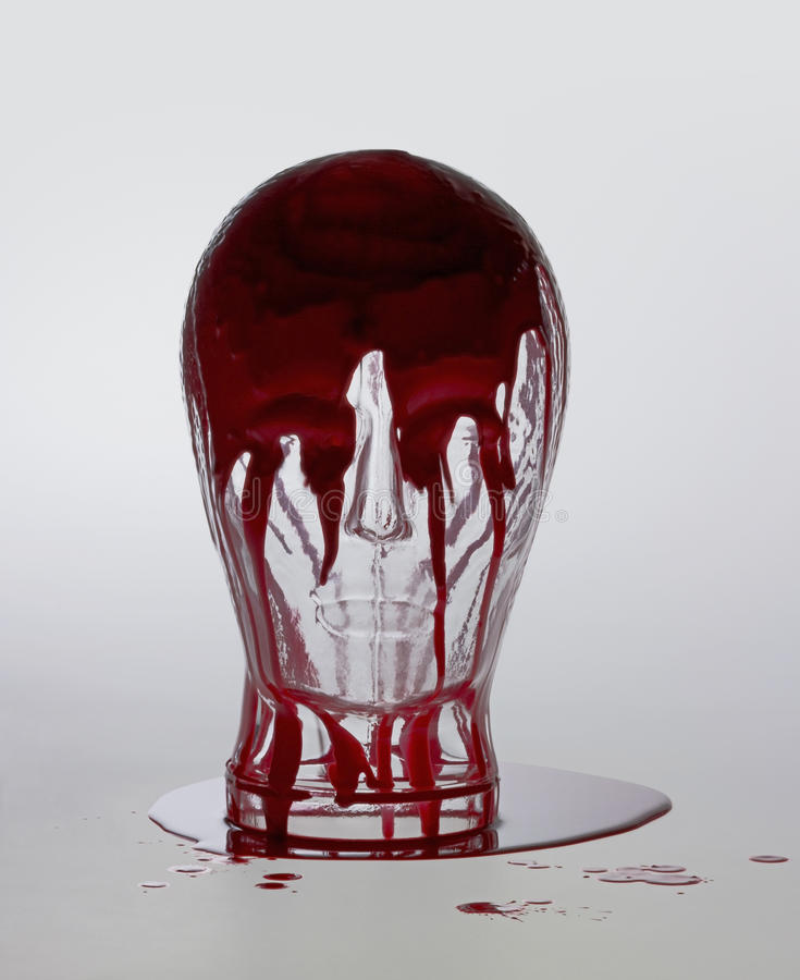 Bloody glass head. Generic human dummy head made of glass, overwhelmed with red fluid in light grey back royalty free stock photo