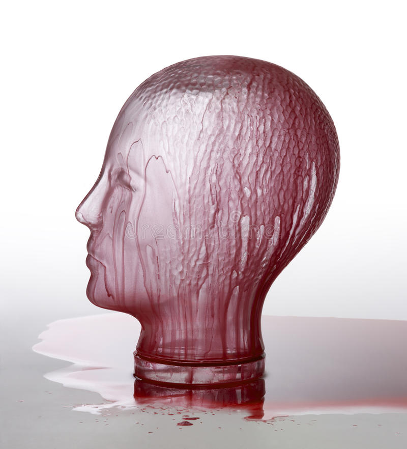 Bloody glass head. Generic human dummy head made of glass, overwhelmed with red fluid in gradient light grey back stock images