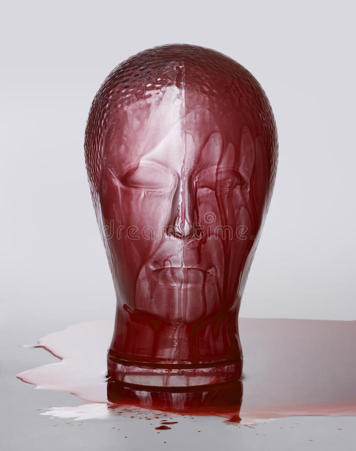 Bloody glass head. Generic human dummy head made of glass, overwhelmed with red fluid in light grey back stock photography