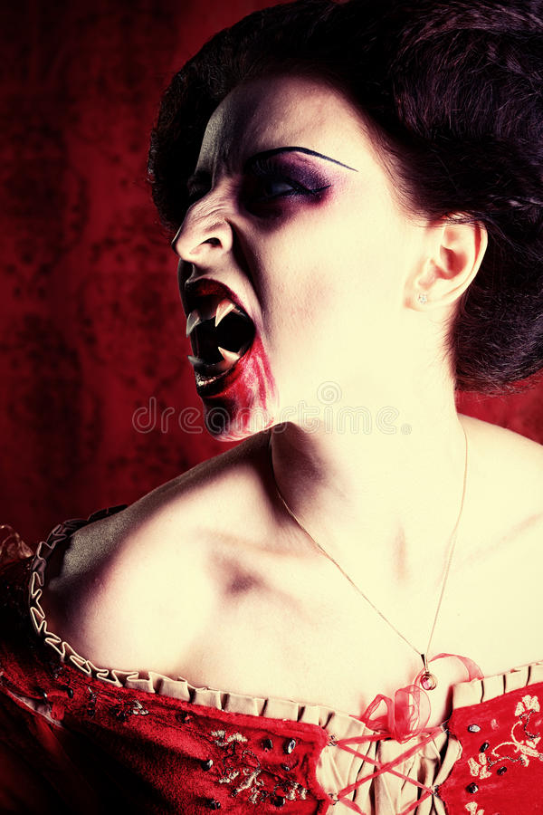 Bloody grin. Portrait of a bloodthirsty female vampire over red vintage background stock photo