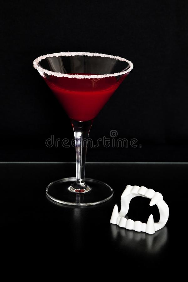 Bloody Halloween vampire drink and fangs on black background with space for copy text. stock photography