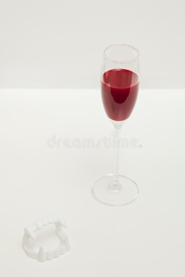 Bloody Halloween vampire drink and fangs on white background. stock photography