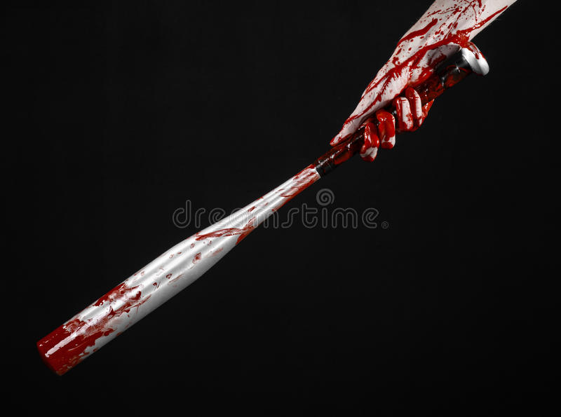 Bloody hand holding a baseball bat, a bloody baseball bat, bat, blood sport, killer, zombies, halloween theme, isolated, black. Background. studio stock image