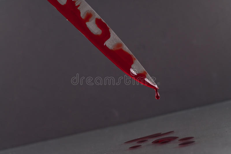 Bloody Knife. Blood Dripping Off Knife Into Puddle royalty free stock images