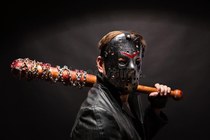 Bloody maniac in mask and black leather coat stock photography