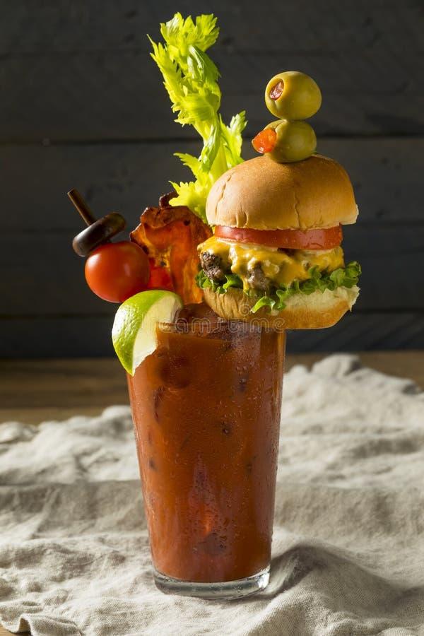 Bloody Mary gourmet gelado frio com um Hamburger foto de stock