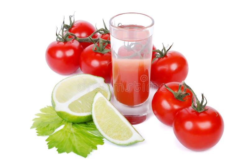 Bloody Marycoctail, limefrukt och grupp av tomater över vit arkivbild