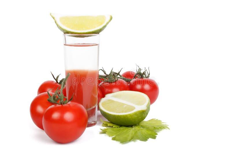 Bloody Marycoctail, limefrukt och grupp av tomater över vit arkivbilder