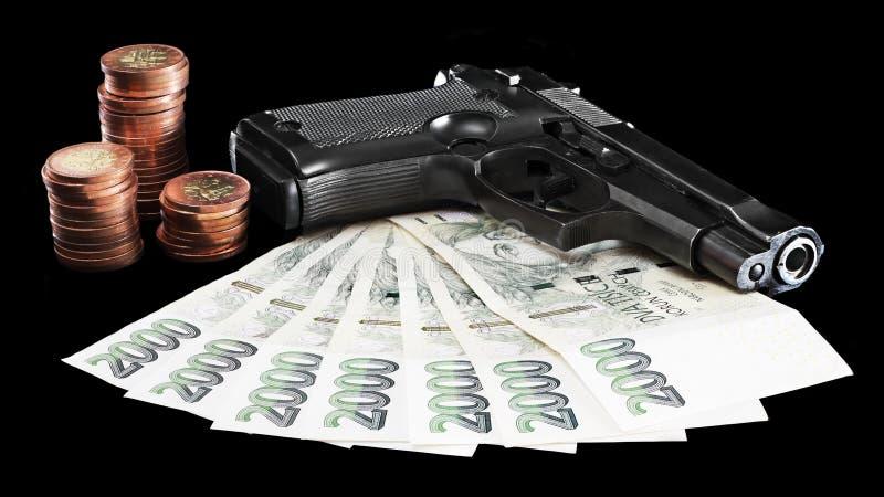 Bloody money. Gun on money symbolising money-related criminality stock images