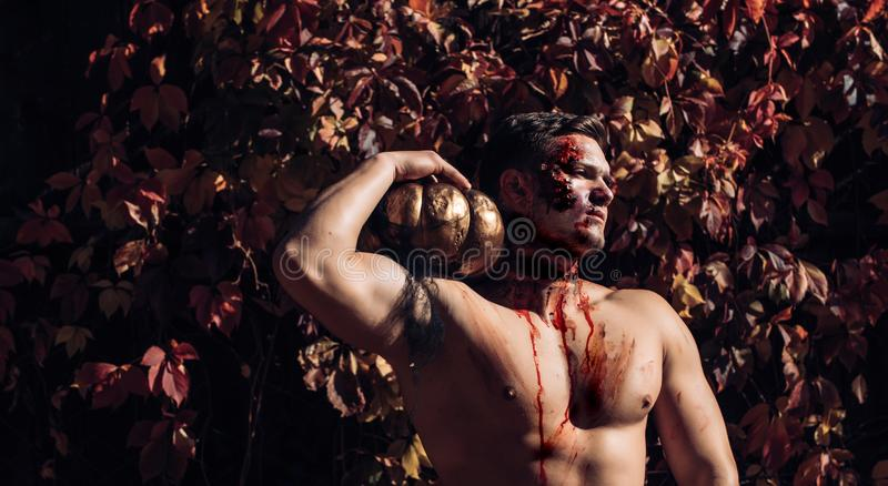 Bloody nude man with head injury, bloody theme, halloween theme, killer. Naked man holding creepy carved halloween. Pumpkin. Skull make up portrait of young man royalty free stock photo