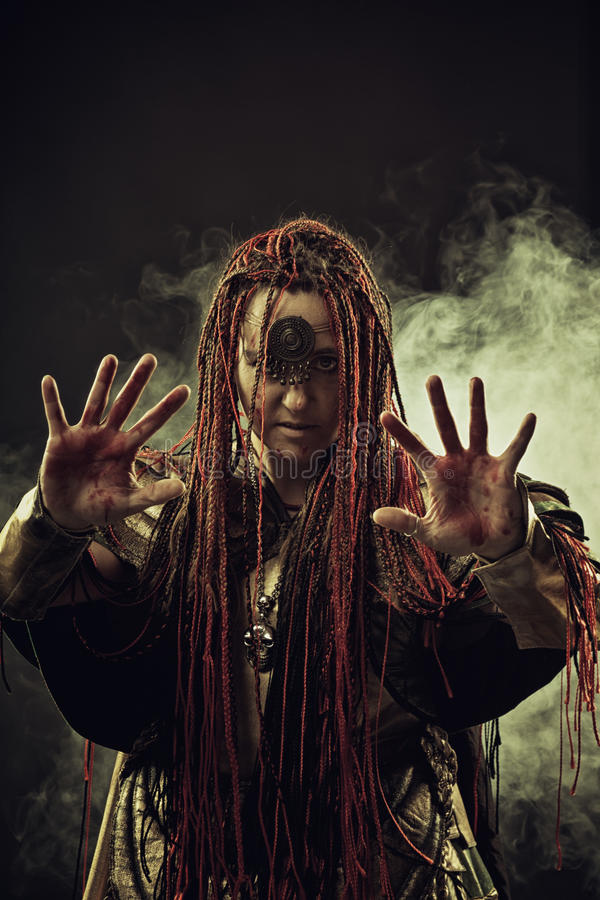 Bloody omen. Wicked shaman with bloody hands in smoke stock photography