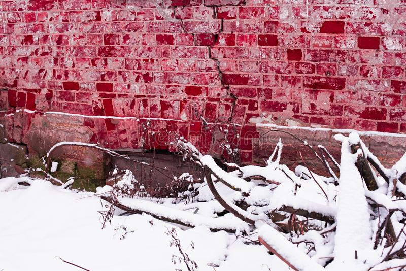 Bloody red brick wall of an abandoned house, broken branches and snow. Bloody red brick wall of an abandoned house stock image