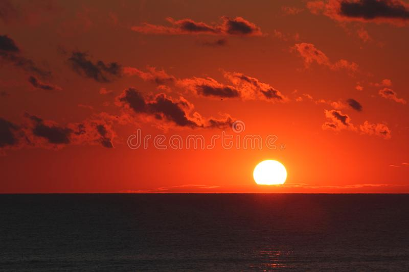 Bloody red cloudy sunrise over the ocean, Japan royalty free stock photography
