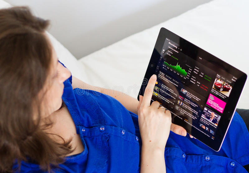Bloomberg. Woman using Bloomberg app on digital tablet to check economic and financial news royalty free stock images