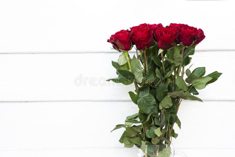 Blooming bouquet of red roses in a clear glass vase. Beautiful blooming bouquet of red roses in a clear glass vase. White wooden board background stock photography