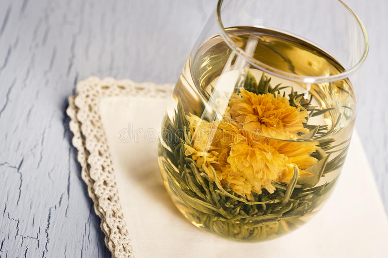 Blooming Flower Hot Green Tea. Blooming Flower Tea is made from flowers and tea leaves, sewn together into a tight ball that opens into a blossom when hot water royalty free stock photo