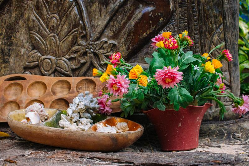 Blooming flowers in pot with wooden candle stand and outdoor decor. Patio design details. Garden in spring. royalty free stock photography