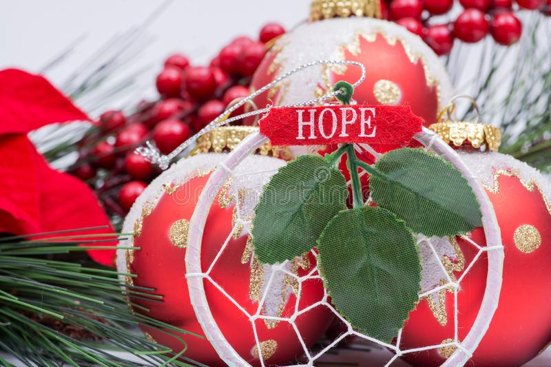 Blooming Holiday Red Poinsettia, Pine and Berry bush and ornament decoration in the form of Christmas tree balls, green leaf. And sign hope royalty free stock images