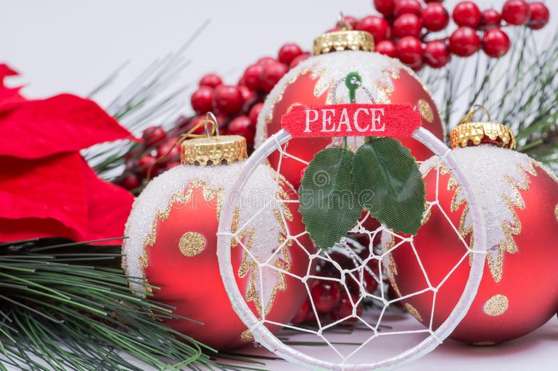 Blooming Holiday Red Poinsettia, Pine and Berry bush and ornament decoration in the form of Christmas tree balls, green leaf. And sign peace stock photos