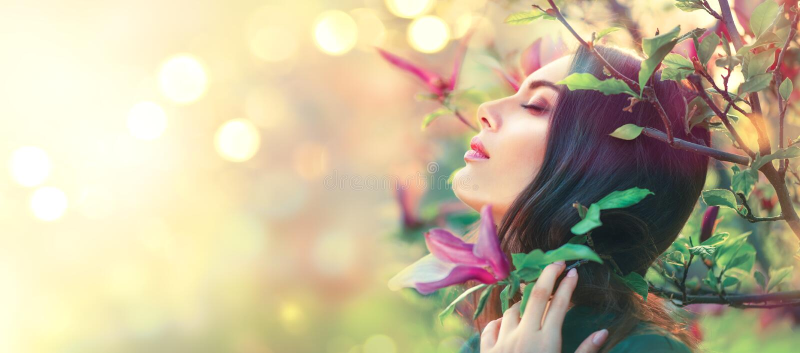 Blooming magnolia trees. Beauty young woman touching and smelling spring magnolia flowers. Happy beautiful girl enjoying nature royalty free stock photos