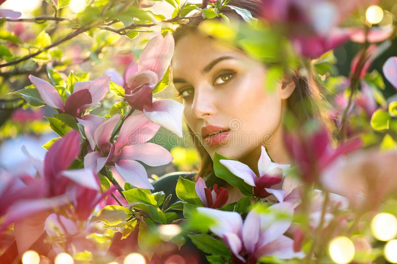 Blooming magnolia trees. Beauty young woman touching and smelling spring magnolia flowers. Happy beautiful girl enjoying nature stock photography