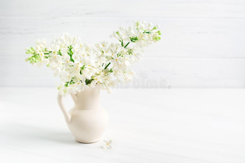 Blooming white lilac in ceramic vase jar with copy space stock photos