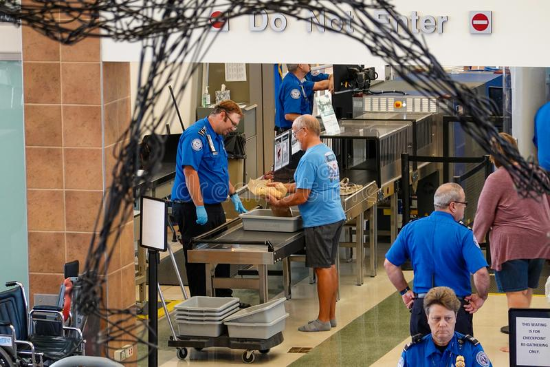 A man getting his sandwich checked at a TSA security line at a small regional airport. Bloomington,IL/USA-8/25/19: A man getting his sandwich checked at a TSA stock photo