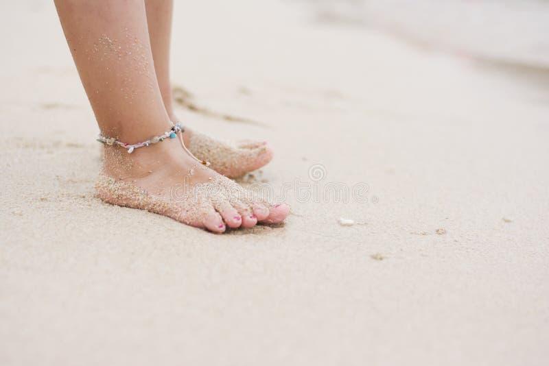 Blootvoets kind met enkelarmband op strand stock foto's