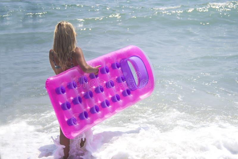 Blootvoets meisje in blauwe bikini bij het overzees Slank lang meisje in het swimwear lopen in het overzees met roze opblaasbaar  stock fotografie