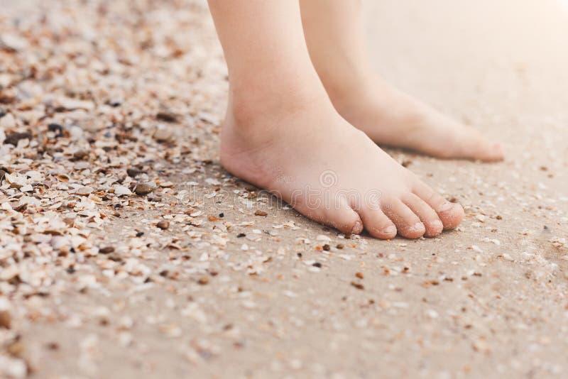 Blootvoetse kindbenen op zand stock foto's