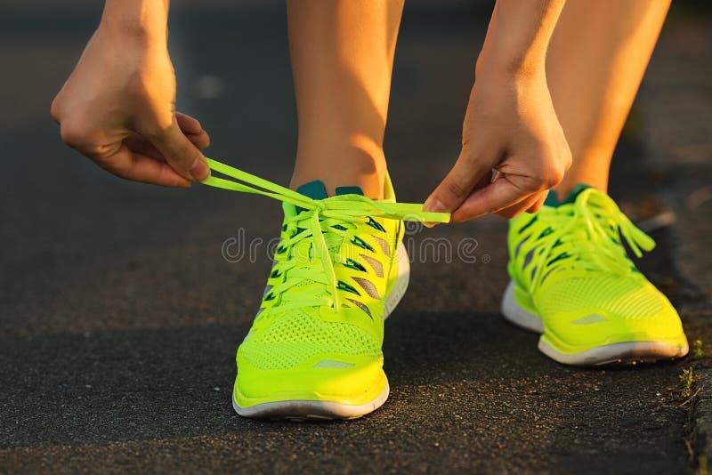 Blootvoetse loopschoenenclose-up Het binden van de vrouw rijgt alvorens in minimalistic blootvoetse loopschoenen op de Brug van B stock foto's