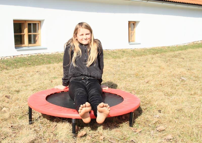 Blootvoetse meisjeszitting op trampoline royalty-vrije stock fotografie