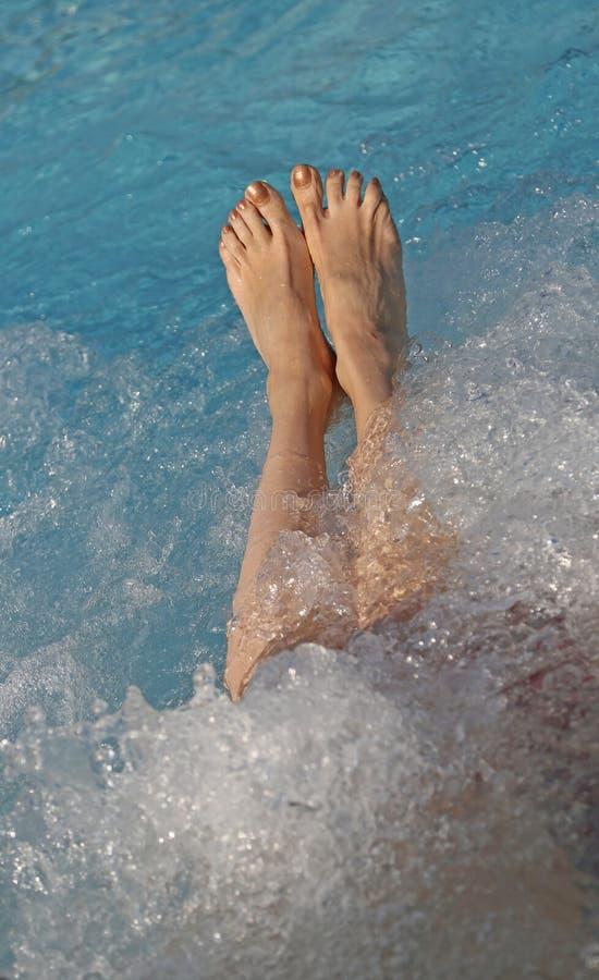 blootvoetse voeten van de jonge vrouw tijdens de hydromassagezitting stock afbeelding