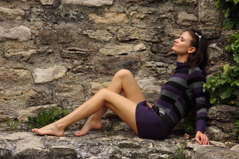 Blootvoetse vrouw die op een rots zonnebaadt stock fotografie
