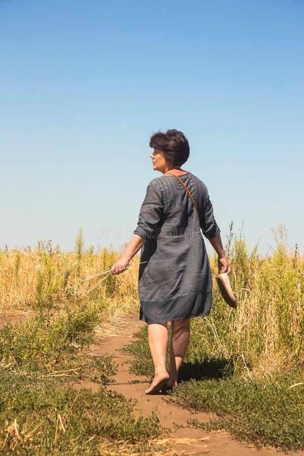 Blootvoetse vrouw op weg door gebied stock fotografie