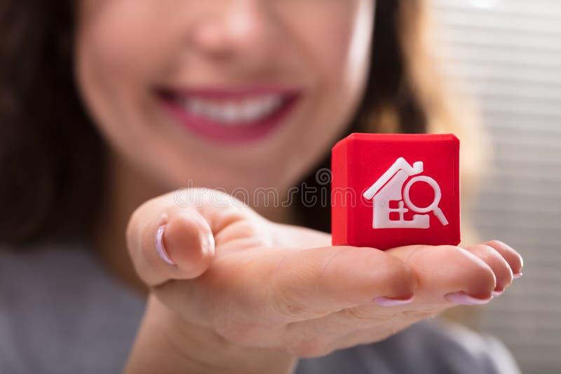 Bloque cúbico de la tenencia de la mujer con el icono casero de la búsqueda imagen de archivo libre de regalías