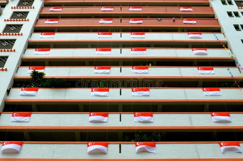 Bloque de apartamentos en Singapur con las banderas para las celebraciones del día nacional imagen de archivo
