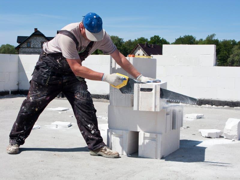 Bloque de cemento del sawing del hombre fotografía de archivo libre de regalías