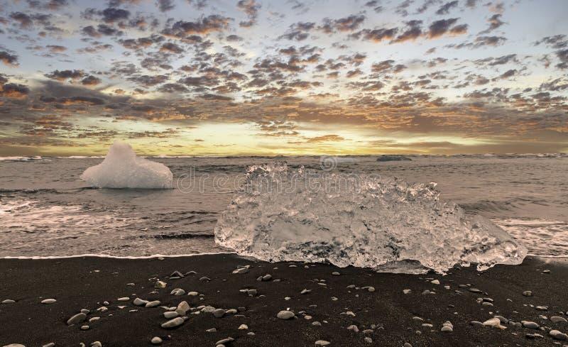 Bloque de hielo en una playa arenosa negra imágenes de archivo libres de regalías