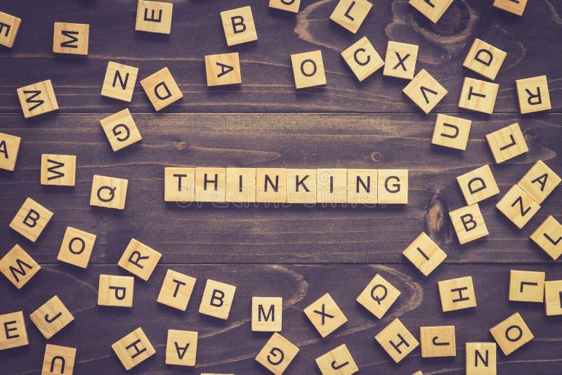 Bloque de madera de pensamiento de la palabra en la tabla para el concepto del negocio foto de archivo