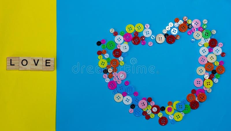 Bloque de madera de la palabra del AMOR y botón colorido foto de archivo