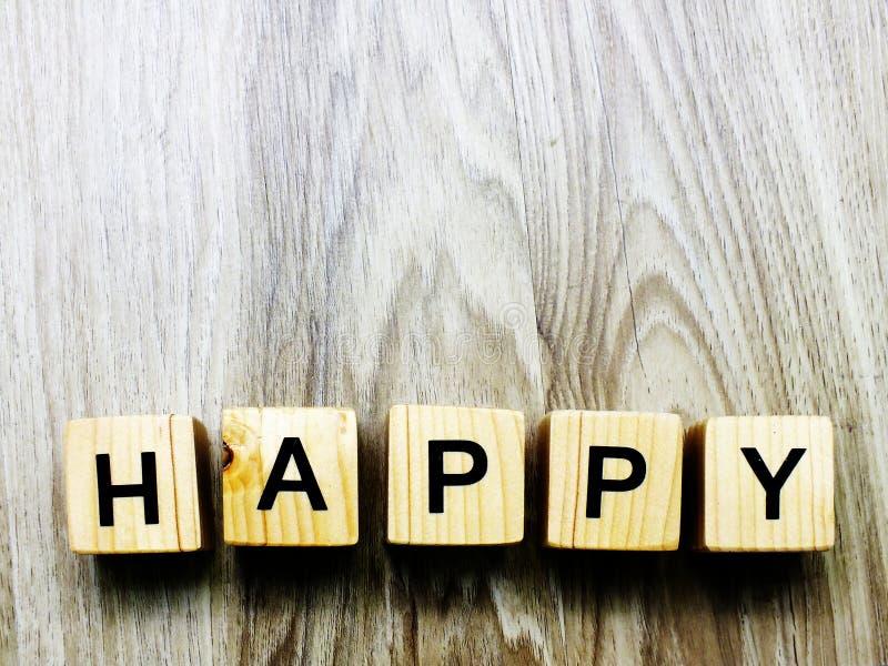 Bloque de madera de la palabra feliz en fondo de madera imagen de archivo