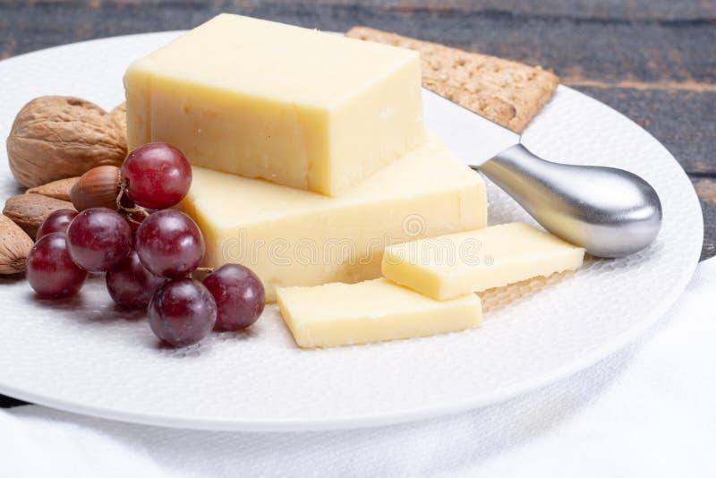 Bloque de queso cheddar envejecido, el tipo más popular de queso adentro foto de archivo libre de regalías