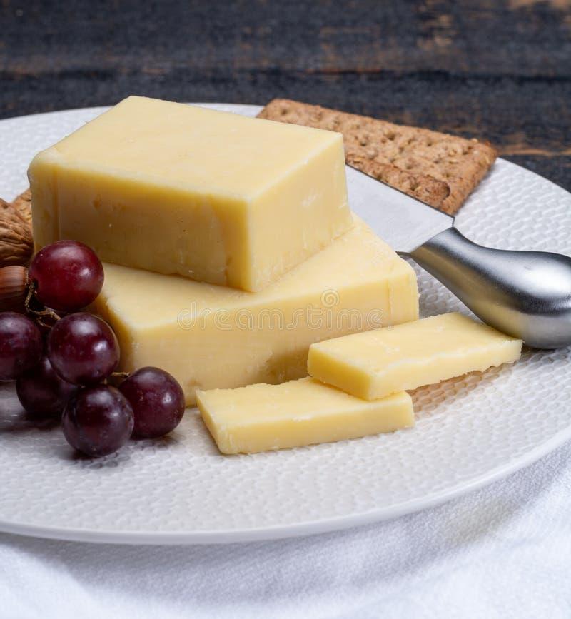 Bloque de queso cheddar envejecido, el tipo más popular de queso adentro foto de archivo