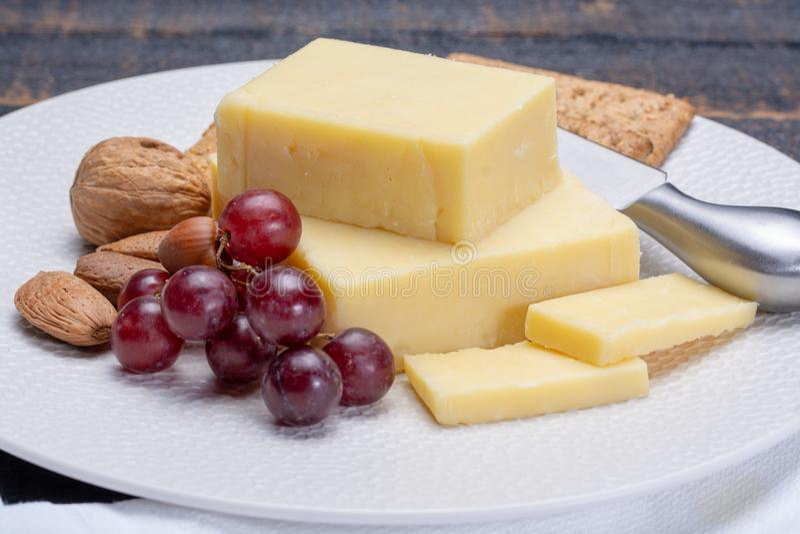 Bloque de queso cheddar envejecido, el tipo más popular de queso adentro fotografía de archivo