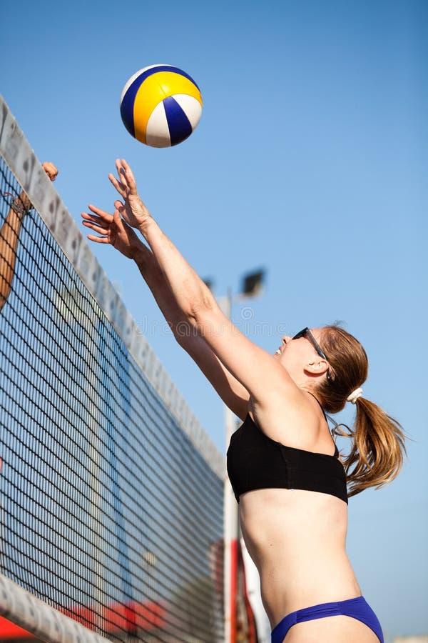 Bloqueo de la mujer del voleibol de playa Bloque en la red imagenes de archivo