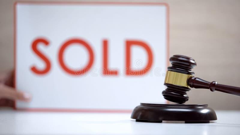 Bloqueo de sonido de pie contra fondo de letrero vendido, decisión judicial, subasta imagenes de archivo