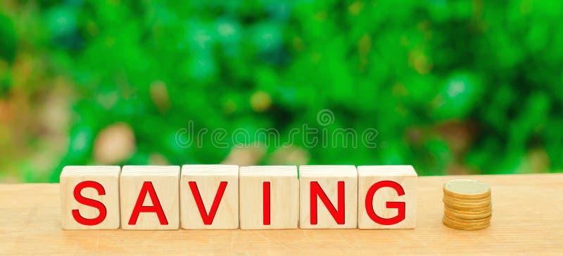 Bloques con el ` del ahorro del ` de la inscripción y monedas El concepto de inversión en un proyecto del negocio, la compra de l fotografía de archivo libre de regalías