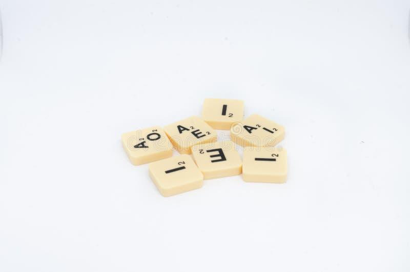 Bloques de la letra del juego de mesa del Scrabble aislados en un fondo blanco imagen de archivo