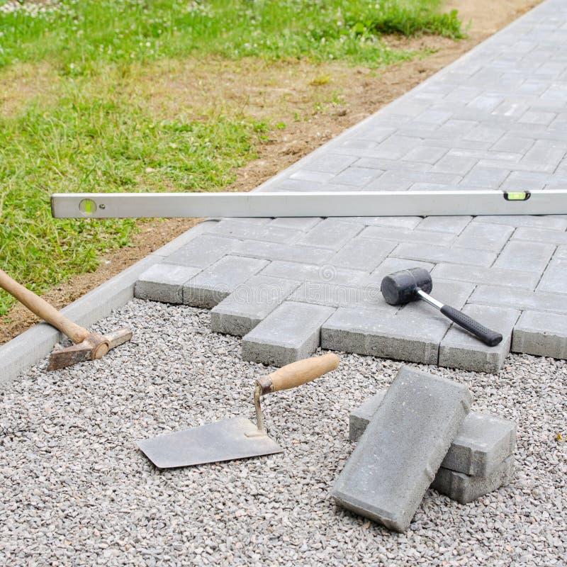 Bloques de la piedra con la herramienta para pavimentar el fondo de la fijación Concepto del arquitecto de Hausework fotografía de archivo